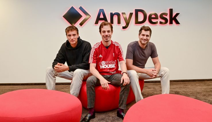 Drei Männer sitzen vor dem AnyDesk-Logo. Der mittlere Mann trägt ein rotes Trikot.